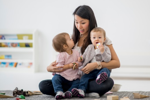Une assistante maternelle avec sur ses genoux deux enfants