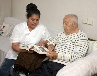 Une infirmière fait la lecture à un monsieur âgé. Ils sont assis dans un canapé blanc.