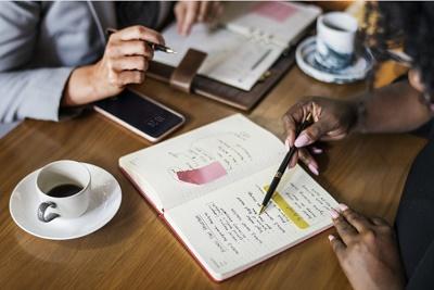Photo d'une table de travail où l'on voit des mains travaillant autour d'un carnet